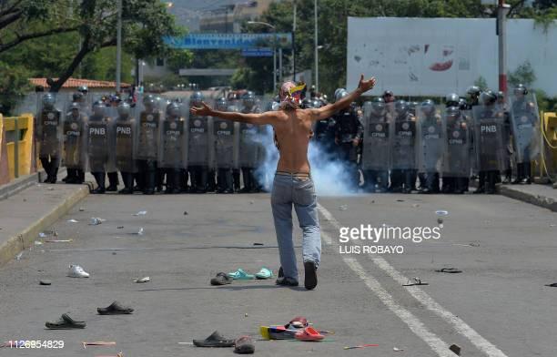 TOPSHOT A demonstrator gestures in front of Venezuelan national policemen standing guard at the Simon Bolivar international bridge in Cucuta Colombia...