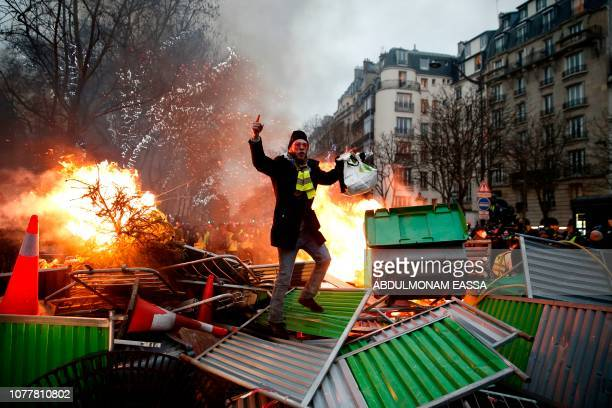 TOPSHOT A demonstrator gestures on a burning barricade on January 5 2019 in Paris during an antigovernment demonstration called by the yellow vest...