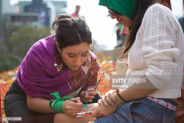 A demonstrator gets her leg painted during a rally on International Women's Day in Mexico City Mexico on Friday March 8 2019 The United Nations first...