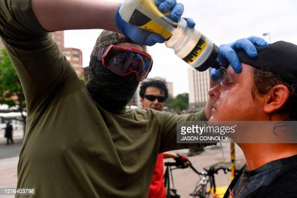 A demonstrator gets his eyes washed after being hit by pepper spray in Denver Colorado on May 30 2020 while protesting the death of George Floyd an...