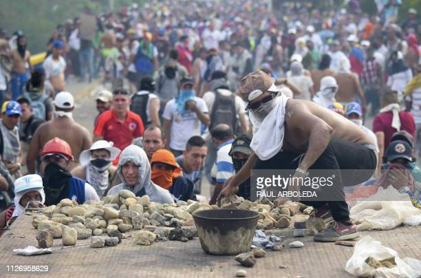 TOPSHOT A demonstrator gets ready to throw a stone in clashes with the security forces at the Francisco de Paula Santander international bridge...