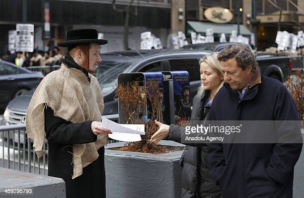 A demonstrator gives a leaflet to a woman in New York City on December 24 2013 Hundreds of Orthodox Jewish students marched to the Israeli Consulate...