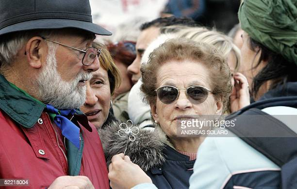 Demonstrator gives a metal symbolic daisy to Giuliana Sgrena's father Franco Sgrena and his wife Antonietta, during a peace march in Rome 19 February...