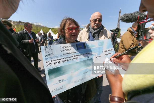 A demonstrator hands a check of one million euros to striking railway workers during a demonstration called by CGT Unsa SUD and CFDT unions on May 3...