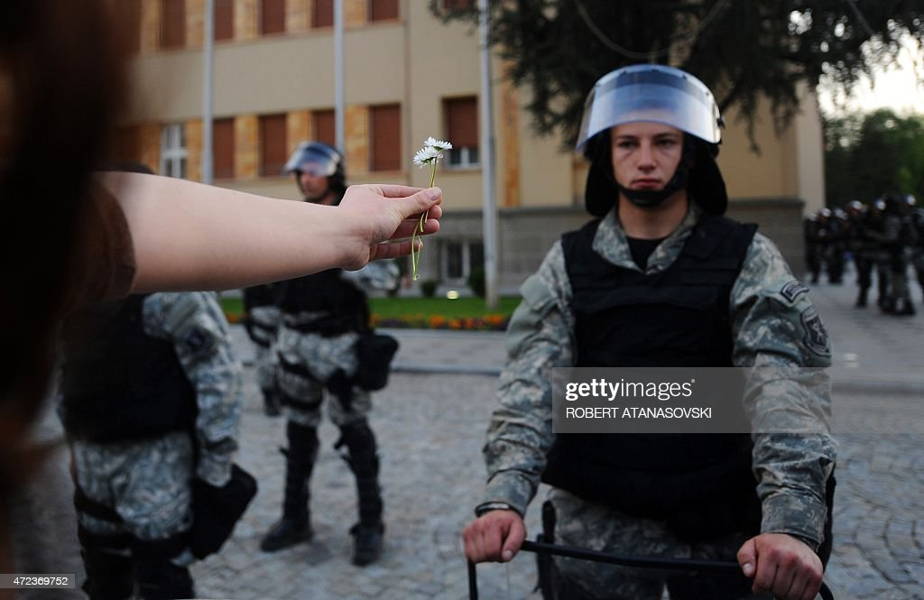 A demonstrator hands a flower to Macedonian riot police officers standing guard outside the Parliament building during an anti-government protest in Skopje on May 6, 2015. Several thousand people protested outside the Parlament building demanding the resignation of Prime Minister Nikola Gruevski, who was accused by the top opposition leader of trying to cover up the death of a 22-year-old beaten by police during post-election celebrations. AFP PHOTOS / ROBERT