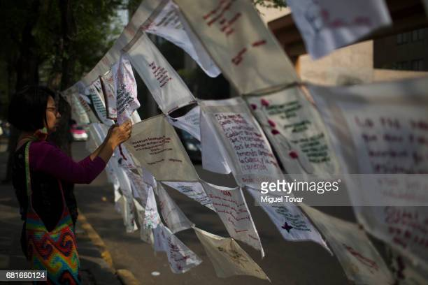 A demonstrator hangs handkerchiefs embroidered by the mothers of the disappeared during a march on Mother's Day on May 10 2017 in Mexico City Mexico...