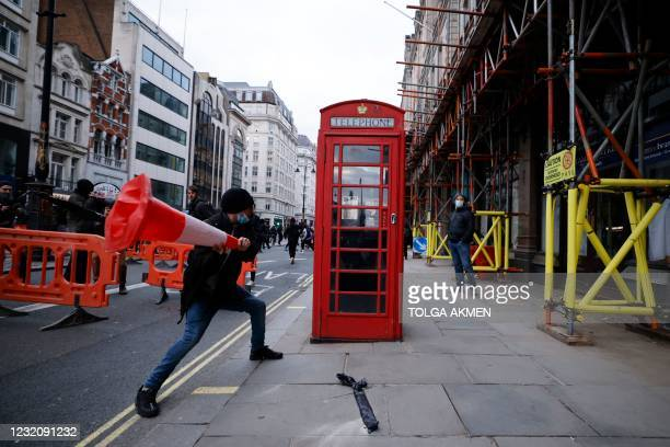 Demonstrator hits a telephone box with a road cone during a 'Kill The Bill' protest against the Government's Police, Crime, Sentencing and Courts...