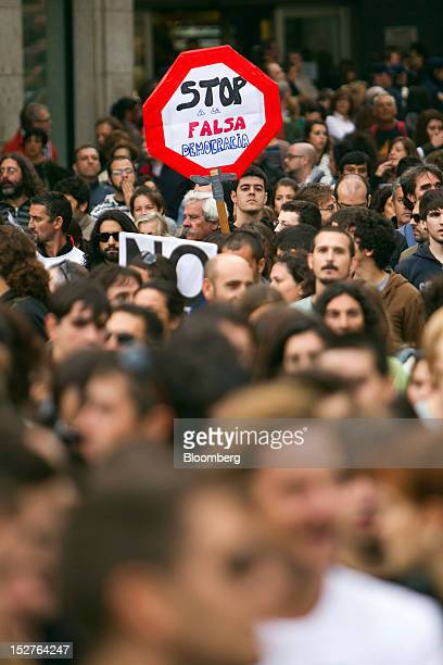 A demonstrator hold a banner which reads Stop Fake Democracy during a protest against the government's austerity measures in the city centre of...