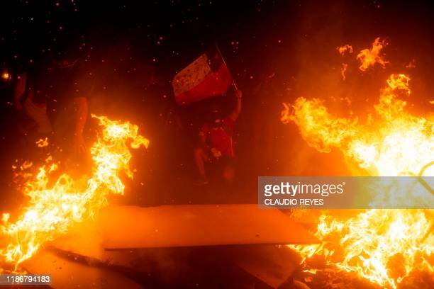 A demonstrator hold a Chilean flag by a bonfire during a protest against the government of Chilean President Sebastian Pinera in Santiago on December...