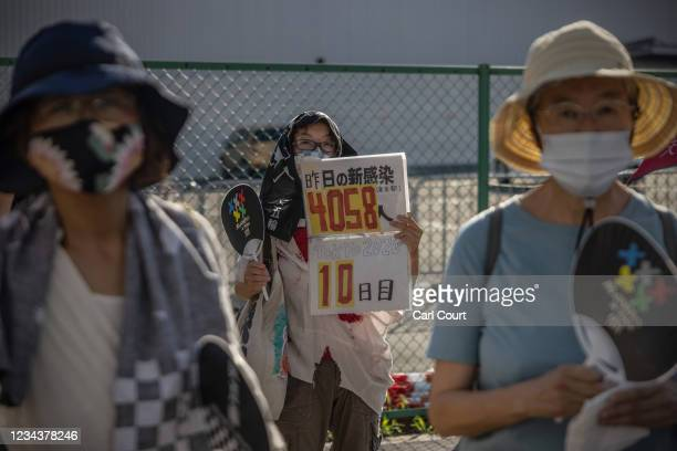 Demonstrator hold a placard showing the number of coronavirus cases from the previous day during an anti-Olympics protest outside Ariake Gymnastics...