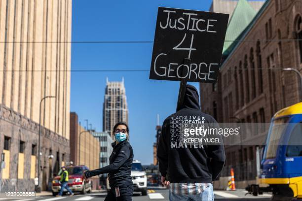 """Demonstrator hold a sign """"Justice for George"""" outside the Hennepin County Government Center during the opening statement of former Minneapolis Police..."""