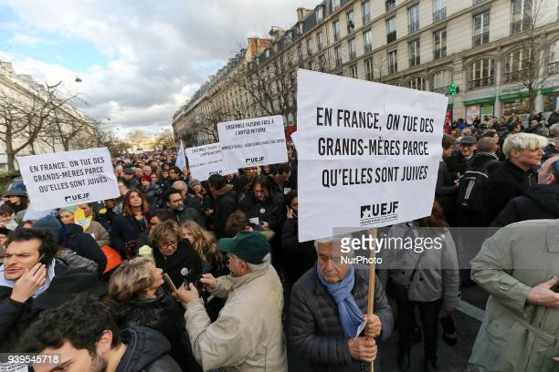 Demonstrator hold a sign reading « In France we kill grandmothers because they are Jewish » during a silent march in Paris on March 28 in memory of...
