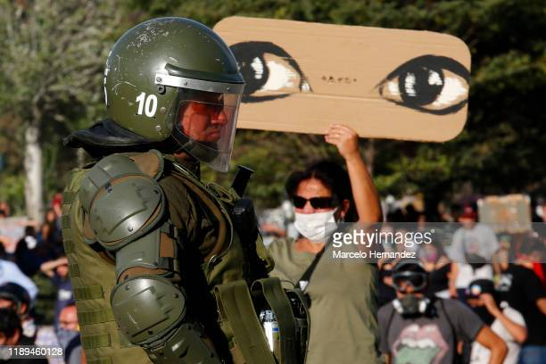 Demonstrator hold a sign with the drawing of eyes in front of a riot police officer during a protest against the government of President Sebastian...