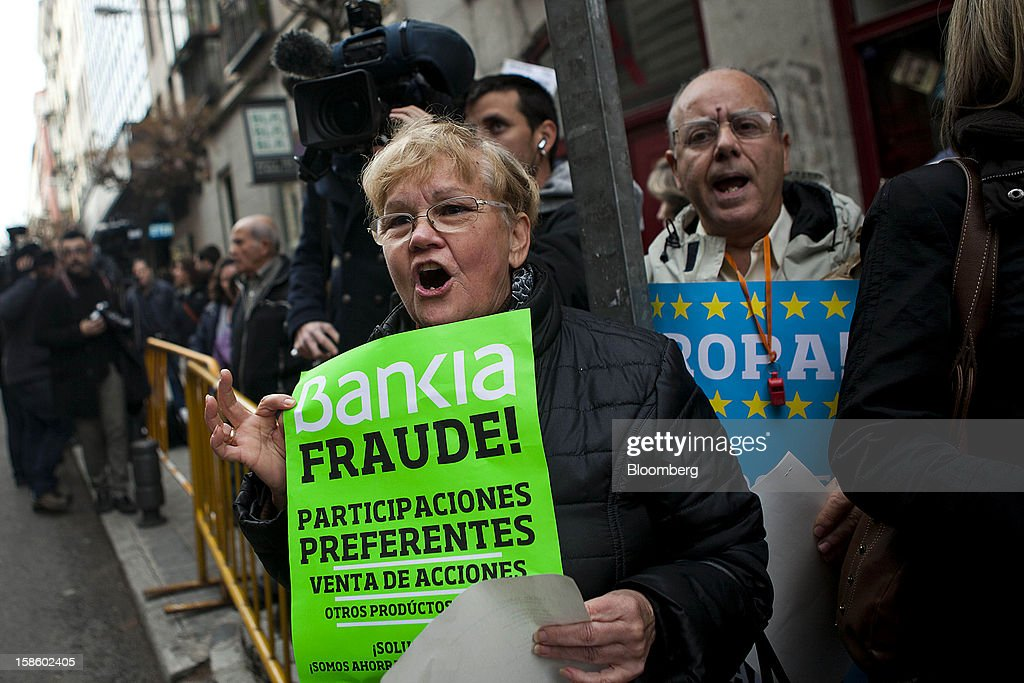 Demonstrator hold signs while chanting during a protest against Rodrigo Rato, former managing director of the International Monetary Fund and ex-chairman of Bankia Group, as he testifies at Spain's national court in Madrid, Spain, on Thursday, Dec. 20, 2012. Rato who led the seven-way savings bank merger in 2010 that formed Bankia, has appeared before lawmakers probing how the lender that was nationalized after seeking 23.5 billion euros ($28.5 billion) of state aid helped trigger a new stage of Europe's debt crisis. Photographer: Angel Navarrete/Bloomberg via Getty Images