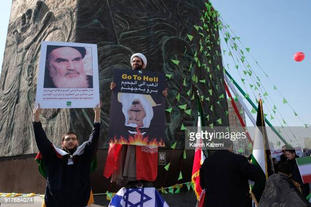 A demonstrator holding a banner with photo of Ayatollah Khomeini stands next to a clergyman wearing the Iranian flag around his shoulders holding a...