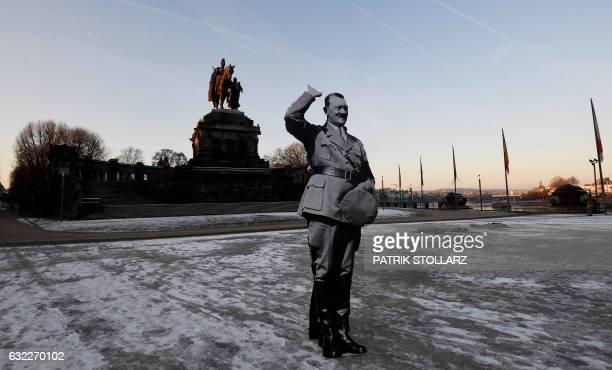 TOPSHOT A demonstrator holding a cardboard cutout depicting German dictator Adolf Hitler stands at the Deutsches Eck memorial during a protest...