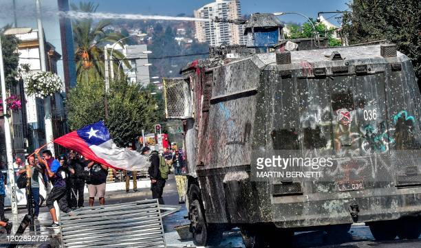 Demonstrator holding a Chilean flag runs away from a police water cannon during a protest against Chilean President Sebastian Pinera's government in...