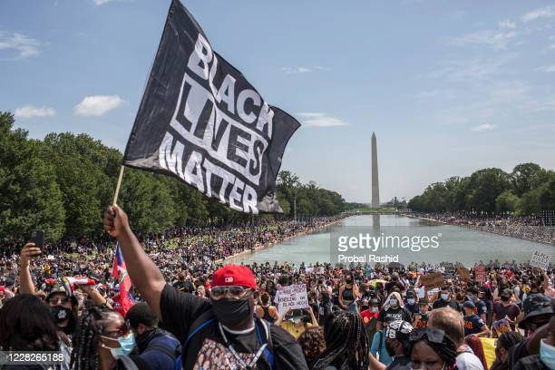 A demonstrator holding a flag with Black Lives Matter written on it while attending the Commitment March Get Your Knee Off Our Necks protest against...