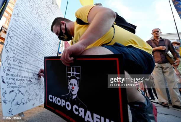 """Demonstrator holding a placard depicting Ukrainian President Volodymyr Zelensky and reading """"Zelensky, you will be jailed soon!"""" signs a petition..."""