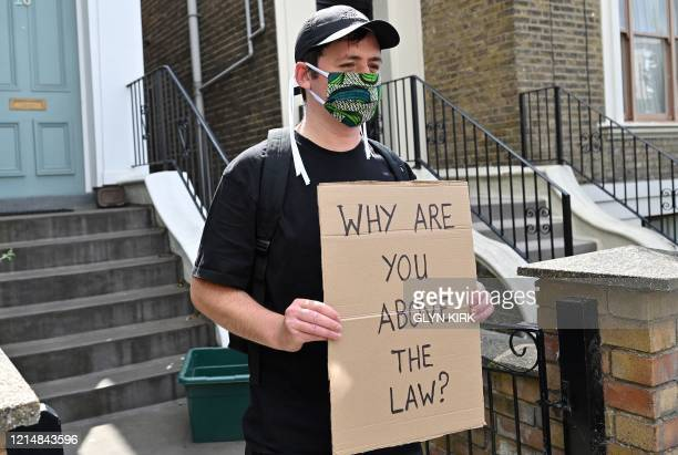 A demonstrator holding a placard that reads Why are you above the law protests outside the home of Number 10 Downing Street special advisor Dominic...