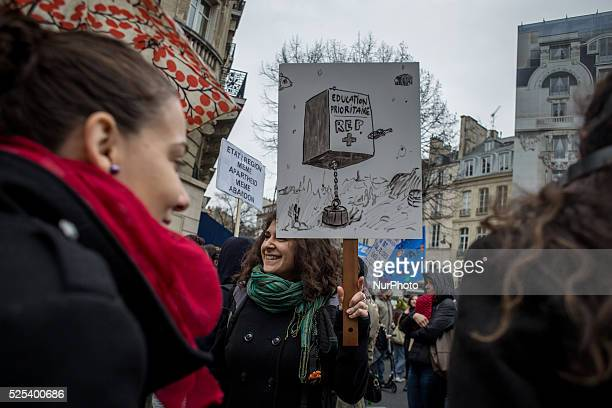 A demonstrator holding a sign with a drawing showing the death of the priority zone education Departmental demonstration of the teacher from Seine St...