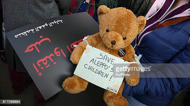 A demonstrator holding a teddy bear and a handmade sign that reads quotSave Aleppo's childrenquot during a protest calling on the British government...