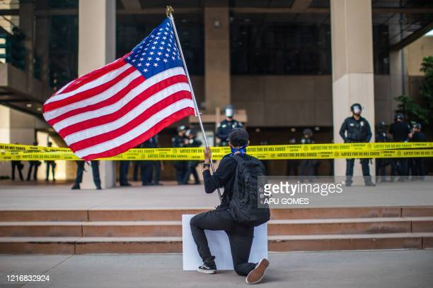 TOPSHOT A demonstrator holding a US flag kneels in front of the Police at the Anaheim City Hall on June 1 2020 in Anaheim California during a...
