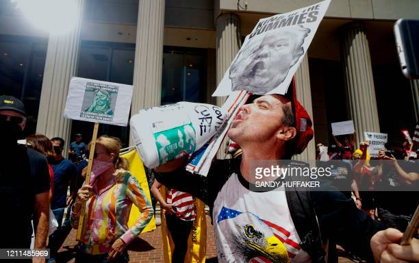 TOPSHOT A demonstrator holding an antiTrump sign pretends to drink from a bottle of bleach during a rally to reopen California and against StayAtHome...
