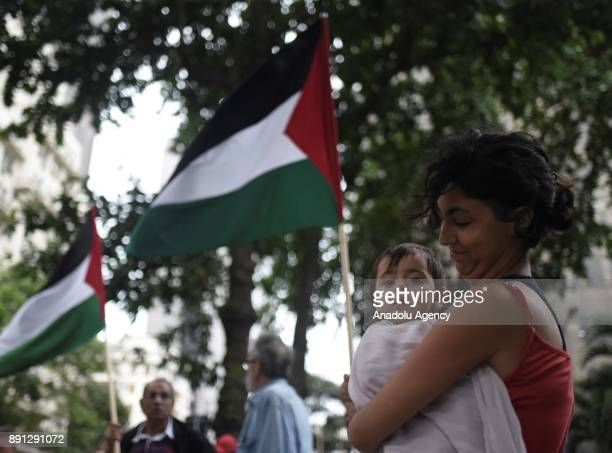 A demonstrator holding her child attends a protest in front of the Consulate of the United States of America against US President Donald Trumps...