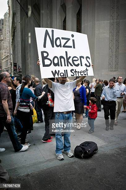 CONTENT] Demonstrator holding placard on the corner of Wall Street and Broadway in New York City's Financial District