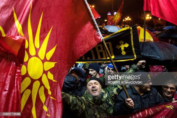 Demonstrator holds a banner as a Macedonian flag floats during a protest against a process of renaming the country North Macedonia in front of the...