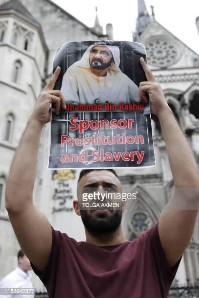 A demonstrator holds a banner during a protest against Dubai's ruler Sheikh Mohammed bin Rashid AlMaktoum outside the High Court in London on July 30...