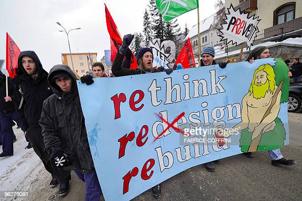 A demonstrator holds a banner during a rally against the annual meeting of the World Economic Forum attended by the world's business and political...