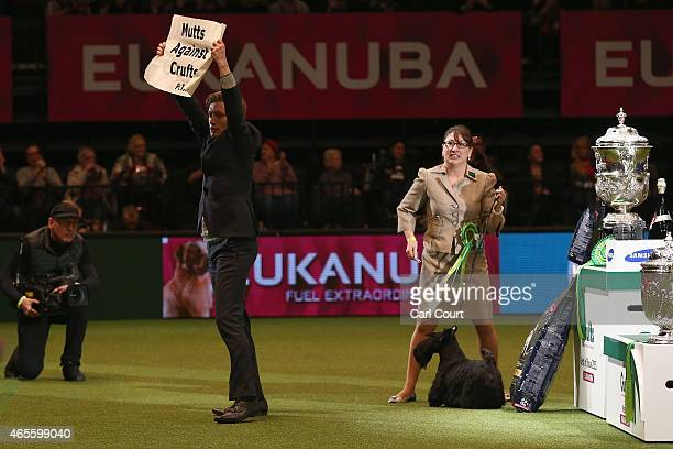 A demonstrator holds a banner onstage during the Best in Show category of Crufts 2015 on the fourth and final day of Crufts dog show at the National...