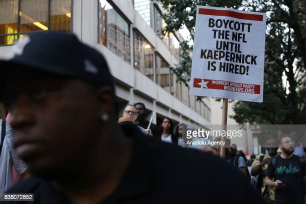 A demonstrator holds a banner reading 'Boycott the NFL Until Kaepernick Is Hired' participate in a rally against the National Football League...