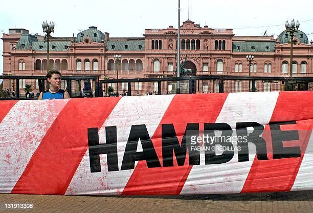 A demonstrator holds a banner reading 'hunger' at the Government Palace 12 December in Buenos Aires during a protest against government economic...