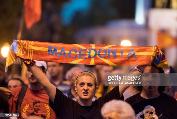 A demonstrator holds a banner reading 'Macedonia' in front of the parliament building in Skopje on June 13 2018 during a protest against the new name...