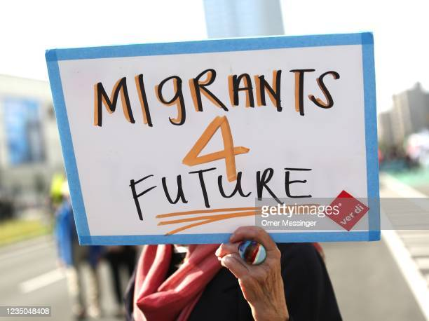 Demonstrator holds a banner reading Migrants 4 future during the Unteilbar protest for social justice and climate change action on September 4, 2021...