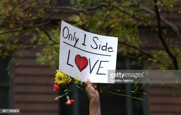 A demonstrator holds a banner reading Only One Side Love during a protest in response to violence erupting at the rally in Charlottesville at Federal...
