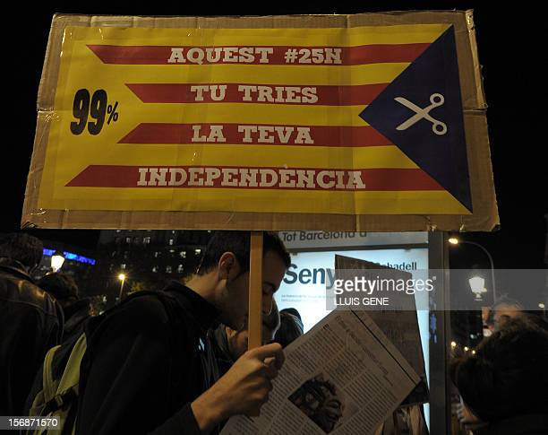 A demonstrator holds a banner reading 'You choose your independence' during a demonstration organized by a platform of several social organizations...