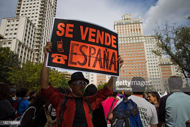 A demonstrator holds a banner which reads Spain on sale during a march organized to protest against the government's austerity measures in the city...