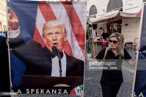 Demonstrator holds a banner with a portrait of the former President of the United States of America Donald Trump during a demonstration in center...