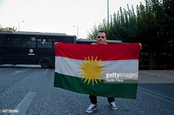 A demonstrator holds a big Kurdish flag standing in front of the Riot police vans that block their way to reach the Turkish embassy Kurdish people...