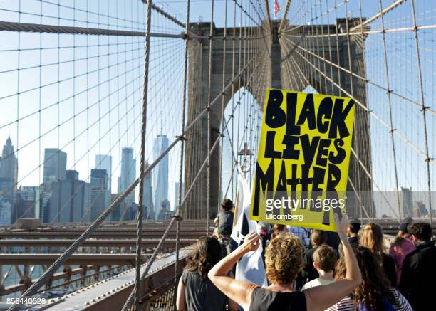 A demonstrator holds a 'Black Lives Matter sign while participating during the March for Racial Justice on the Brooklyn Bridge in the Brooklyn...