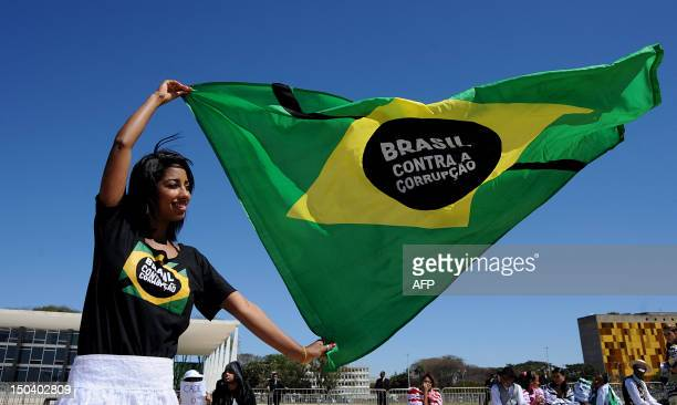 A demonstrator holds a Brazilian flag during a protest in front of the Supreme Court where the trial known as 'mensalao' is being held in Brasilia...