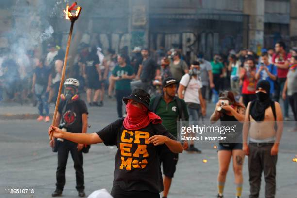 Demonstrator holds a burning spear during protests against president Piñera at Plaza Italia ona on December 4, 2019 in Santiago, Chile. Today...