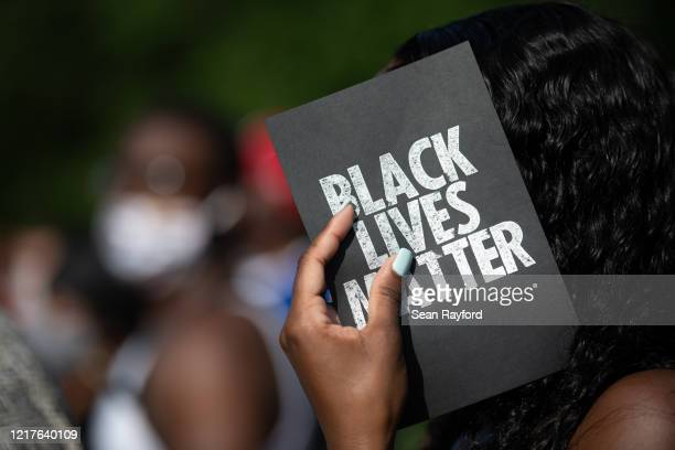 A demonstrator holds a card that reads Black Lives Matter outside of the Glynn County courthouse during a court appearance by Gregory and Travis...