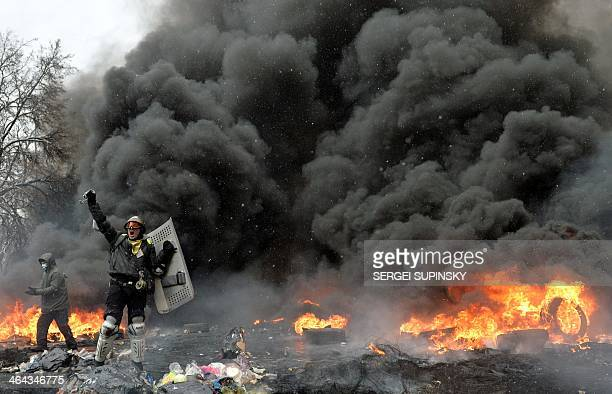 A demonstrator holds a chain and riot police shield during clashes between protestors and police in the center of Kiev on January 22 2014 At least...