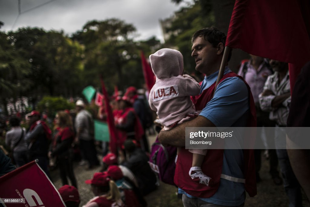 A demonstrator holds a child wearing a jacket displaying the name 'Lula' during a protest in support of Luiz Inacio Lula da Silva, former president of Brazil, on the day Lula is scheduled to testify before Sergio Moro, the lead jurist in the sprawling corruption probe known as Operation Carwash, in Curitiba, Brazil, on Wednesday, May 10, 2017. Thousands of Brazilians are descending on the southern city of Curitiba before a showdown between one of the most popular leaders in the country's history and its most famous judge at a hearing that could determine the republic's future. Photographer: Dado Galdieri/Bloomberg via Getty Images