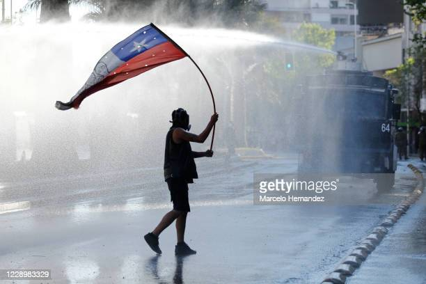 Demonstrator holds a Chilean flag as a water cannon fires against demonstrators during a protest against a wide range of issues including inequality,...